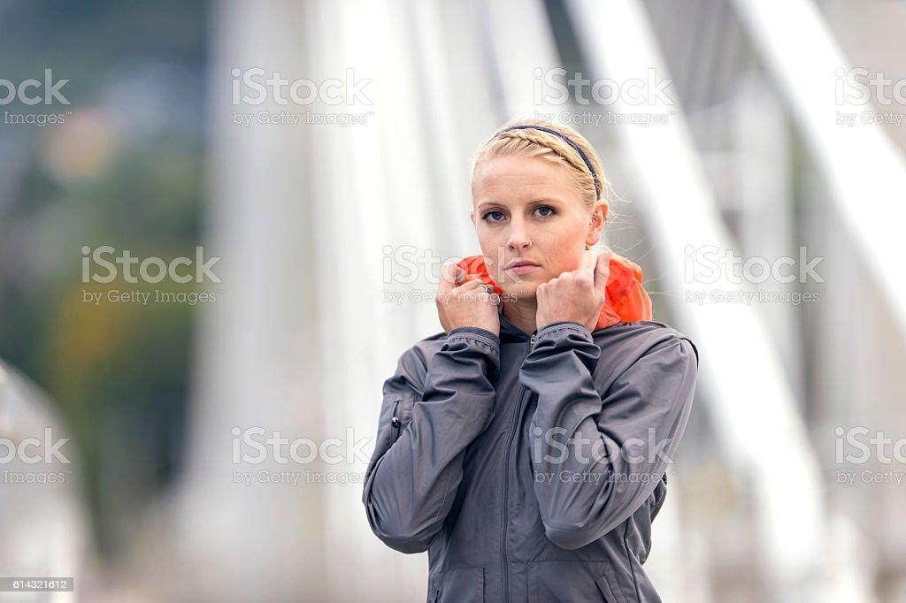 Adult female athlete pulling up her wind breaker stock photo