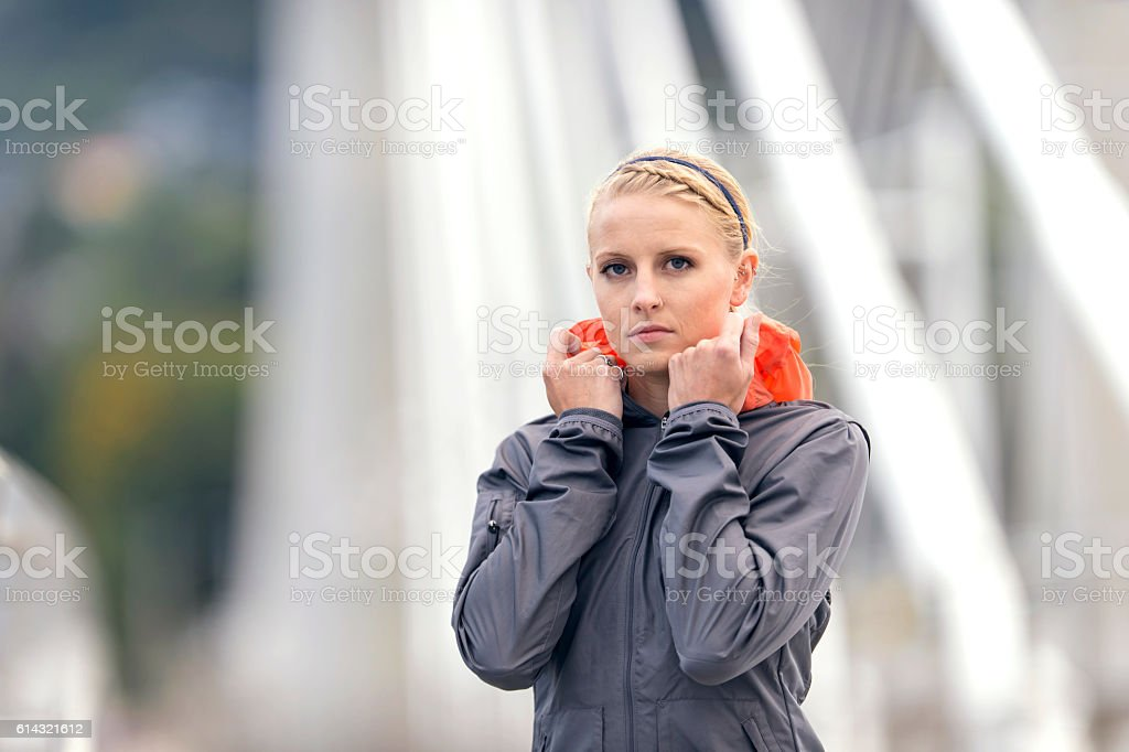 Adult female athlete pulling up her wind breaker stock photo