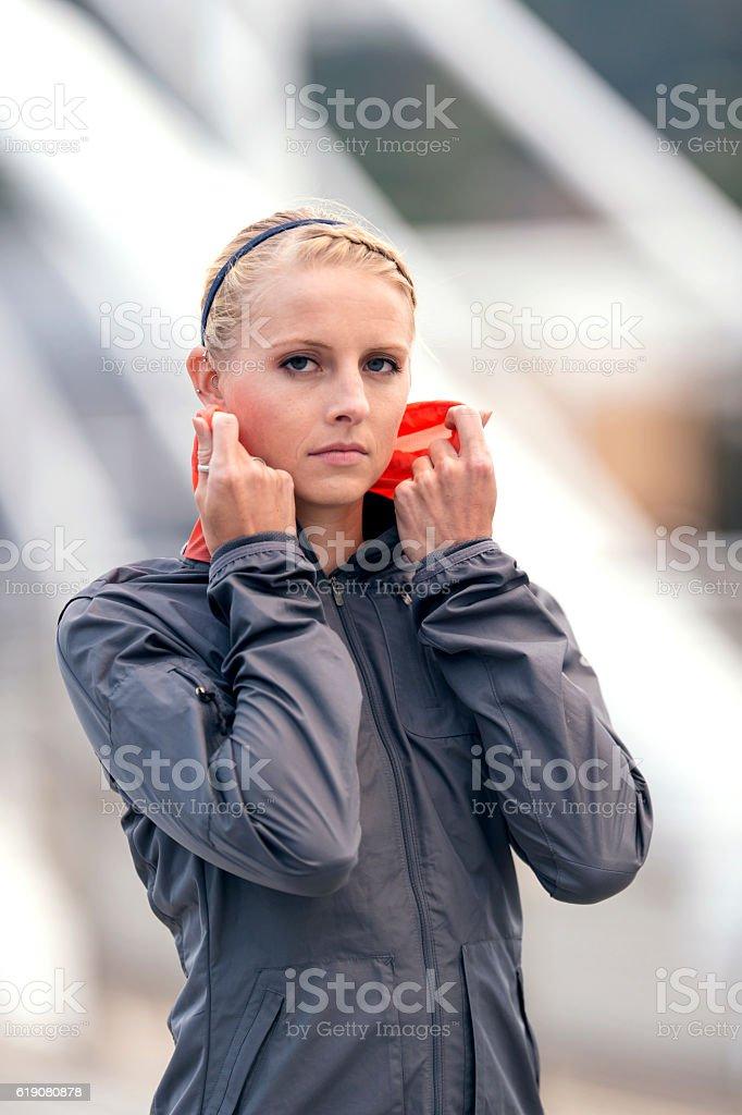 Adult female athlete pulling up the hood on her windbreaker stock photo