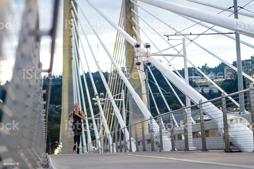 Adult female athlete running across a bridge at sunset stock photo