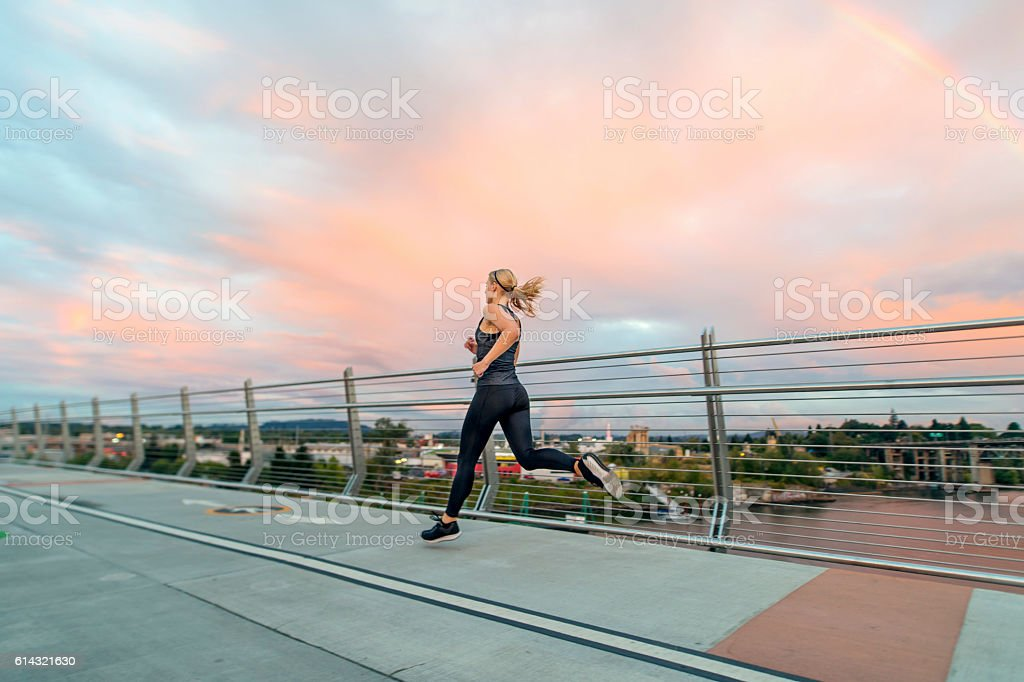 Adult female athlete sprinting across a bridge wearing athletic attire stock photo