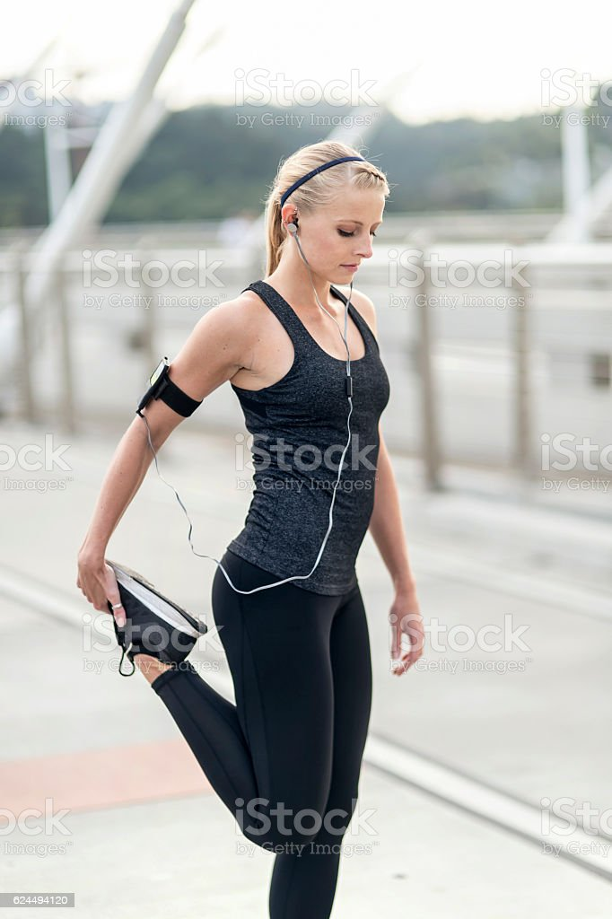 Adult female athlete stretching before her morning jog stock photo