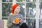 Adult female cancer patient drinking tea and looking hopeful