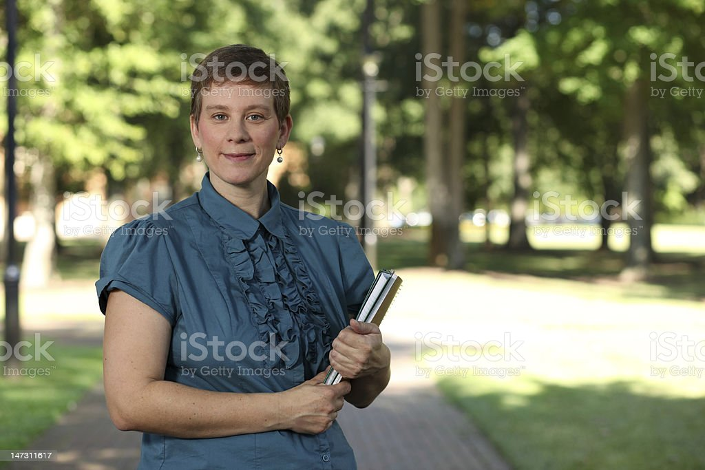 Adult female college student holding books smiles at camera. stock photo