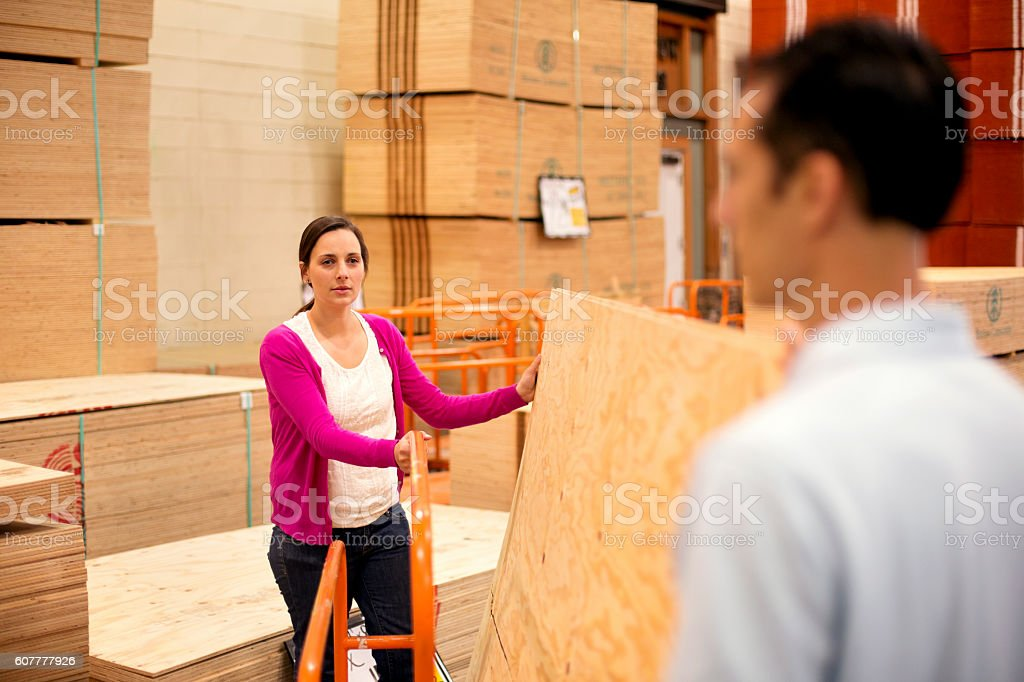 Adult female loading plywood sheets on a cart stock photo