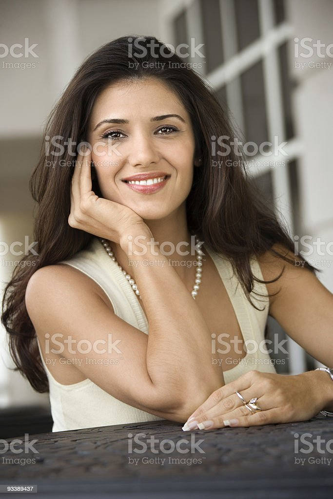 Adult female sitting at table. stock photo
