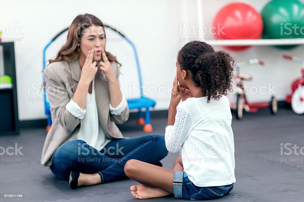 Adult female therapist guiding young girl in speech therapy stock photo
