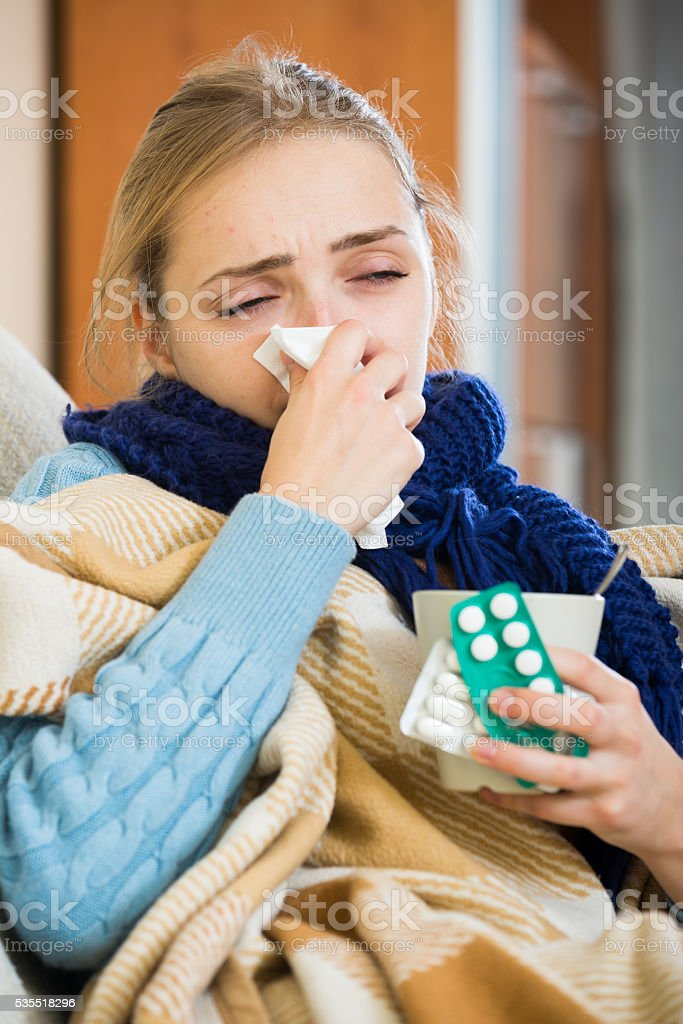 Adult female under blanket with flu attack indoors stock photo