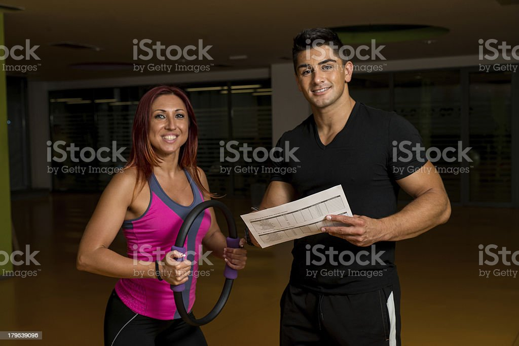 Adult female with personal trainer at gym royalty-free stock photo