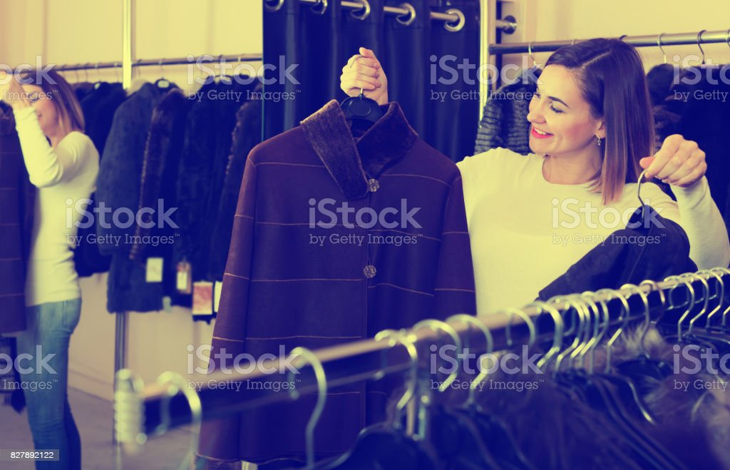 Adult girl deciding on warm brown coat stock photo