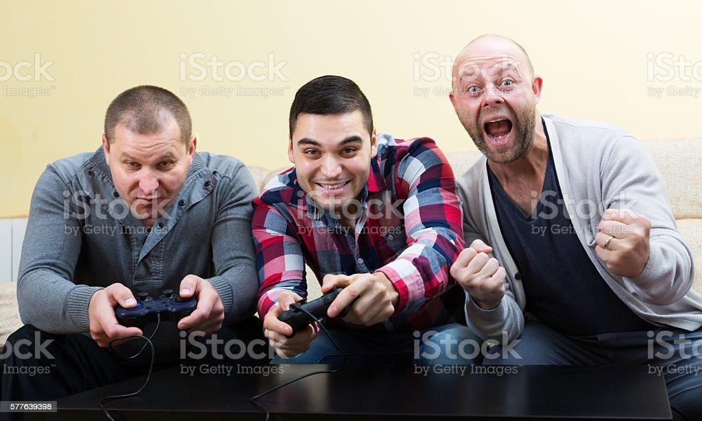 Adult guys sitting with joysticks stock photo