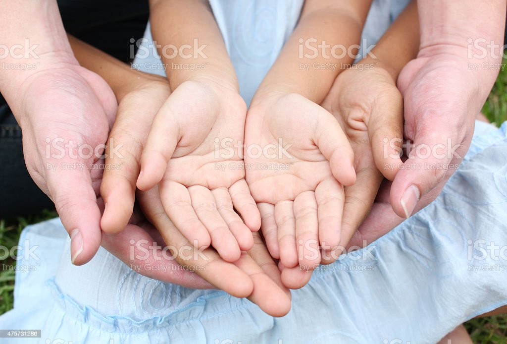 Adult hands holding kid hands stock photo