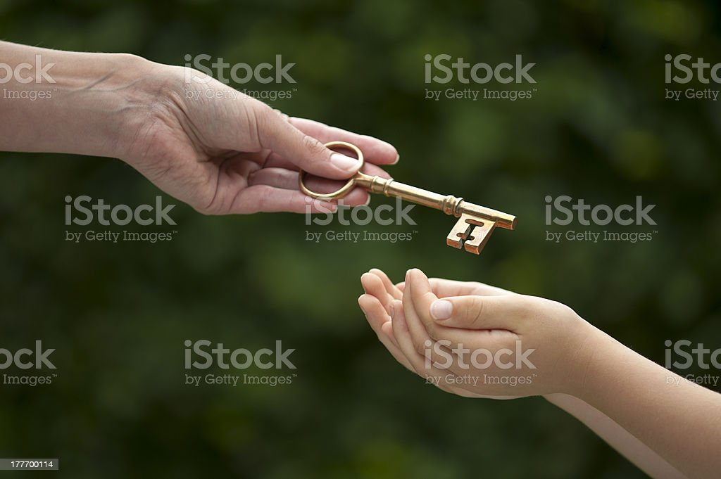adult hands key to child stock photo