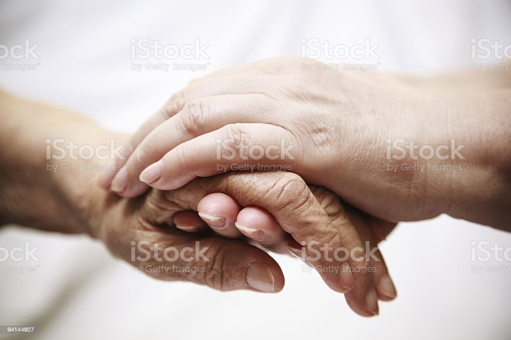 adult helping senior in hospital stock photo