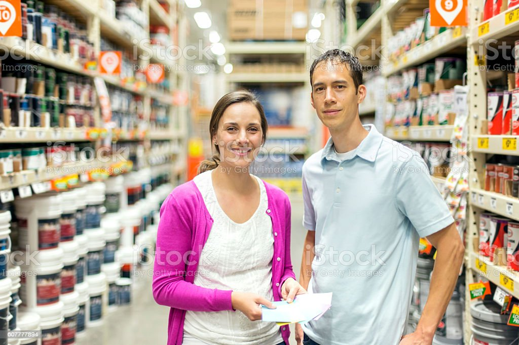 Adult heterosexual couple holding a shopping list and smiling stock photo