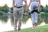 Adult heterosexual pregnant couple holding hands and baby shoes