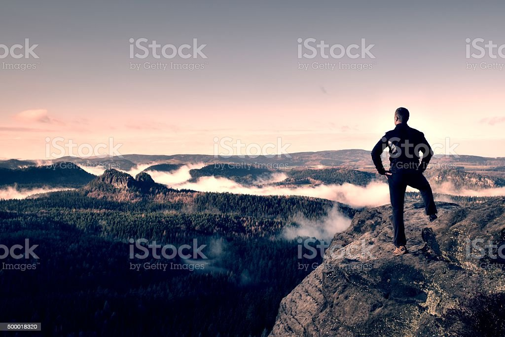 Adult hike watching over the misty and foggy morning valley stock photo