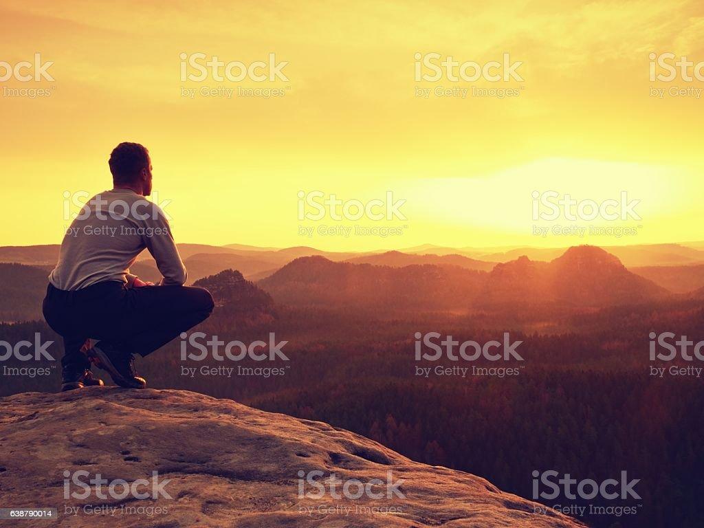 Adult hiker sit on mountain  edge. Man enjoying evening stock photo