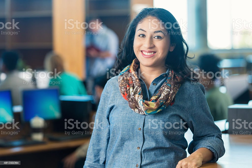 Adult Hispanic college student standing in library stock photo
