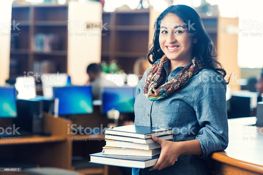 Adult Hispanic student holding stack of books in college library stock photo