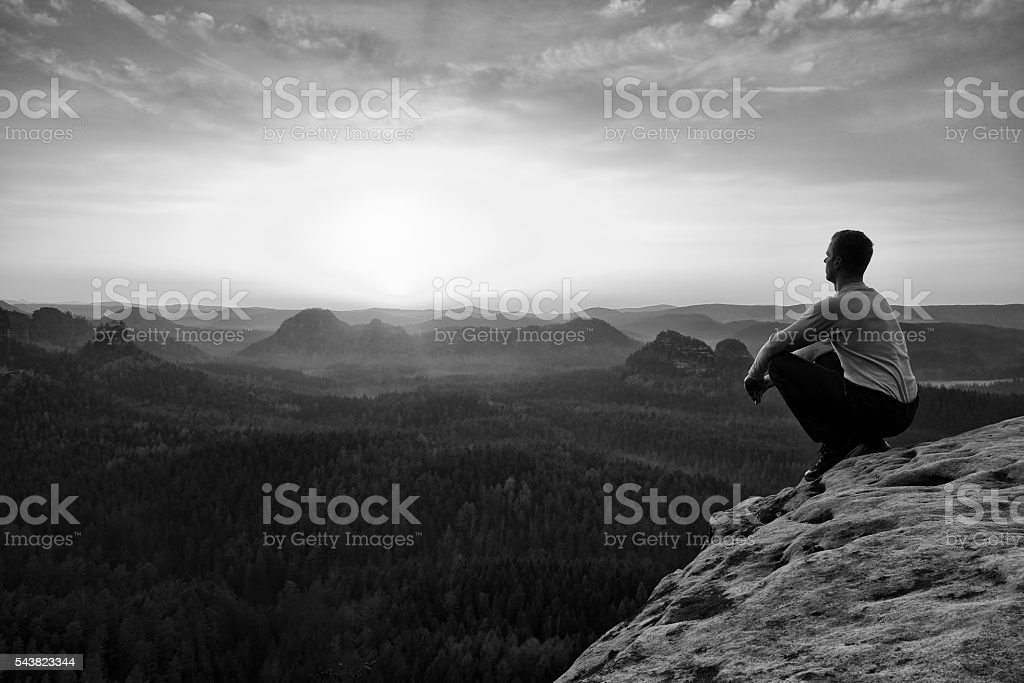 Adult in black trousers, jacket sit on cliff's edge stock photo