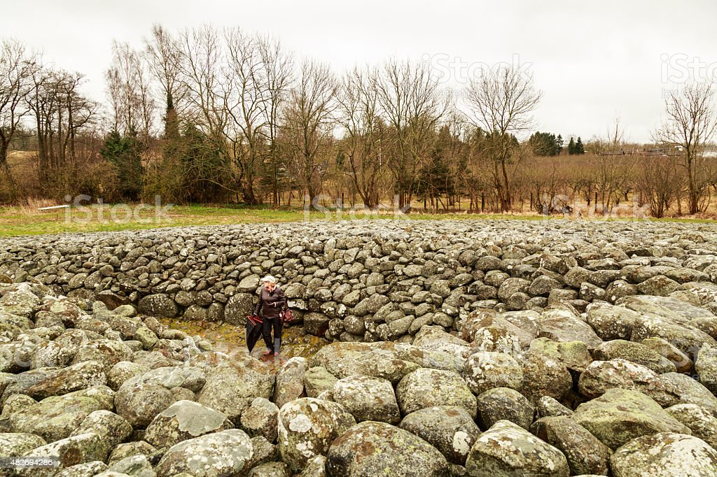 Adult lady in humid wether visiting a cairn stock photo