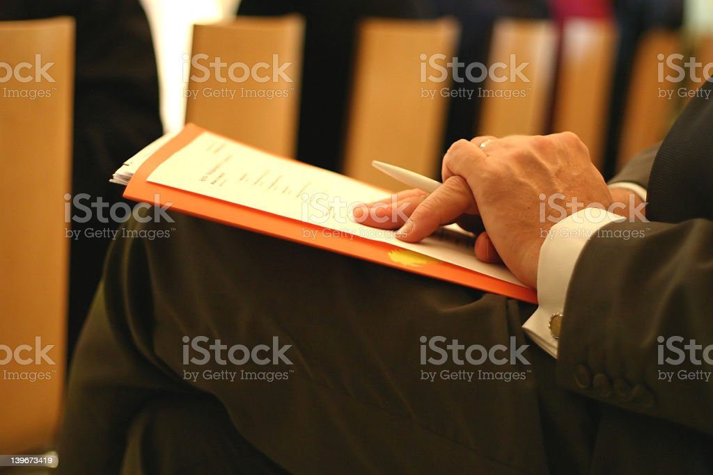 Adult make taking notes in an office setting stock photo