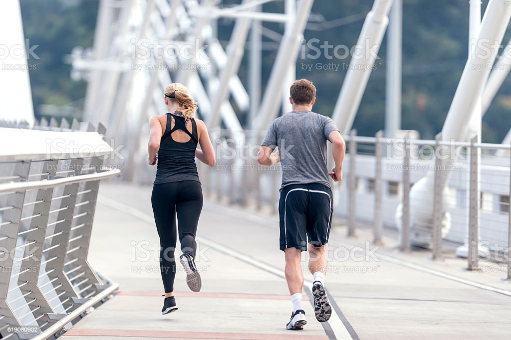 Adult male and female athletes running across a bridge stock photo