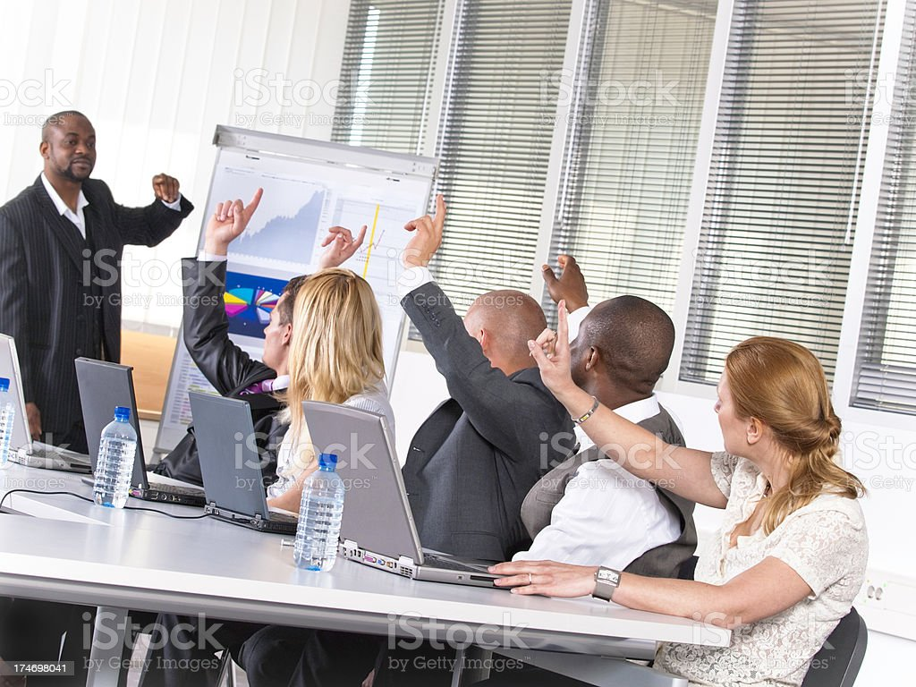 Adult male and female students raising hands at a seminar royalty-free stock photo