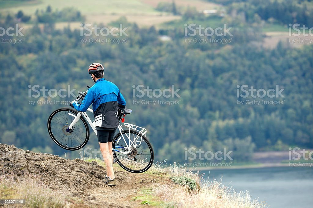 Adult male athlete carrying bike along rocky trail stock photo