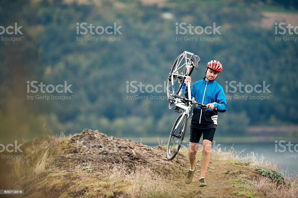 Adult male biker carrying bicycle along ridge trail stock photo
