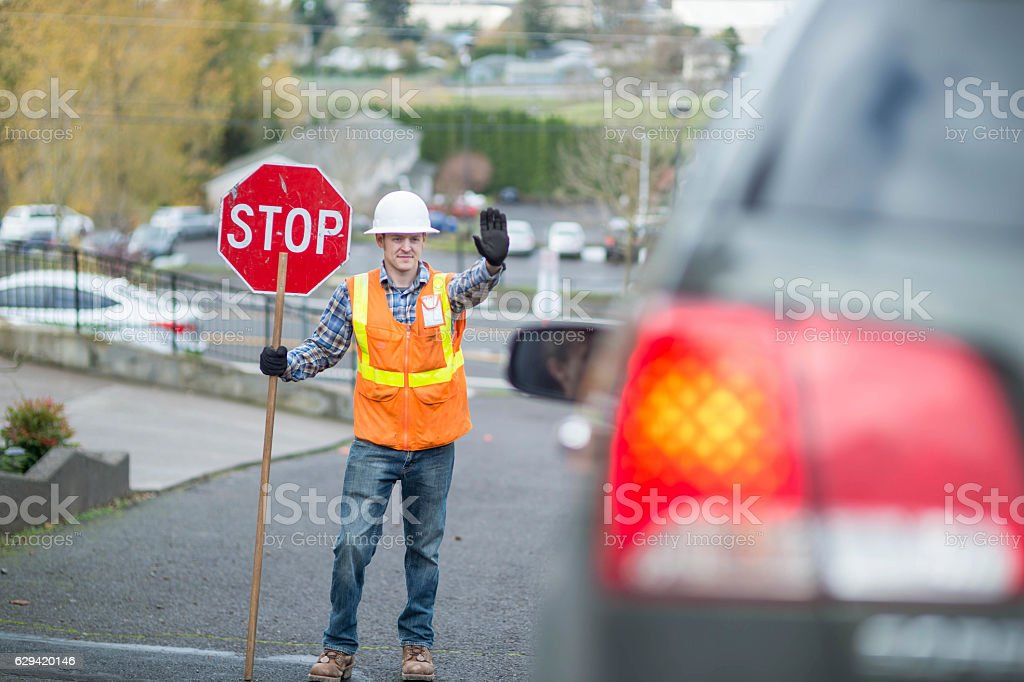 Adult male construction worker stopping traffic stock photo