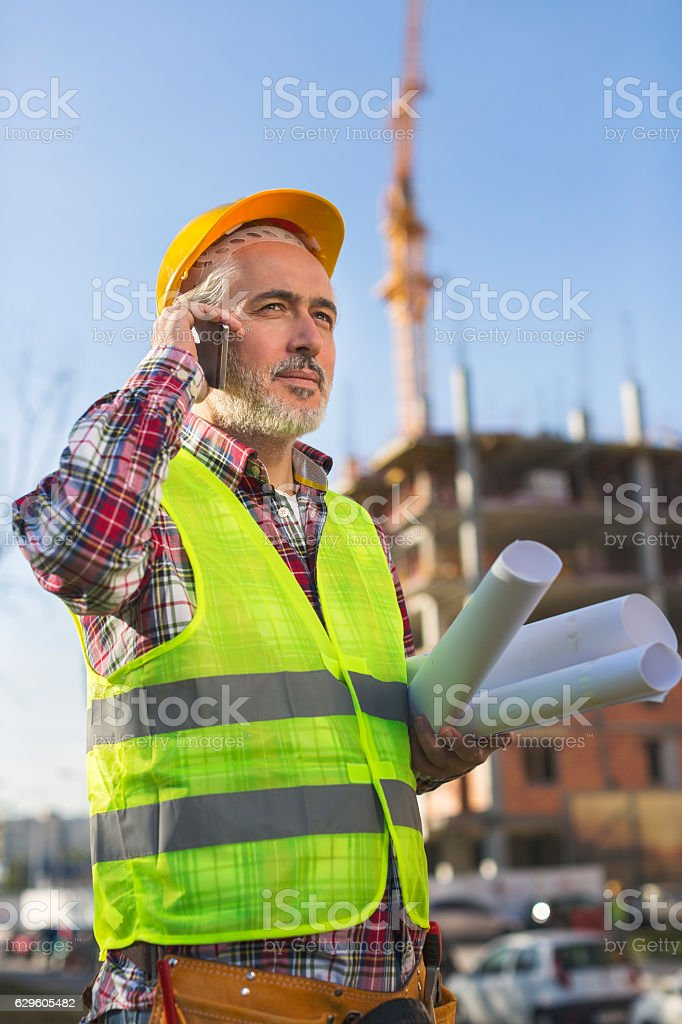 Adult male engineer holding blueprints while talking on his phone royalty-free stock photo