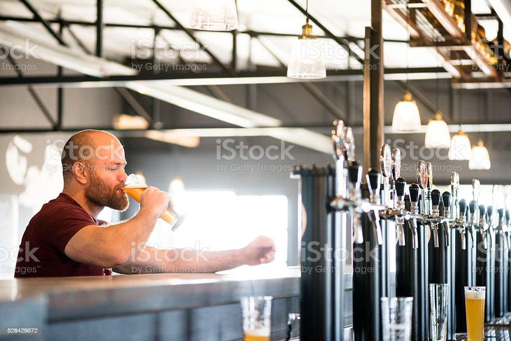 Adult Male Enjoying A Good Craft Beer At The Brewery stock photo