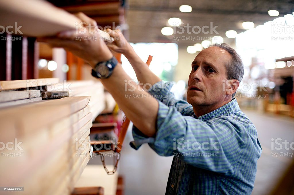 Adult male hardware store employee lifting boards stock photo