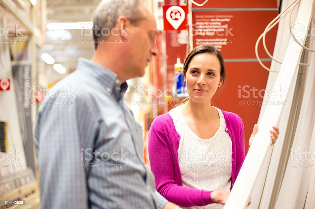 Adult male hardware store employee talking with female shopper stock photo