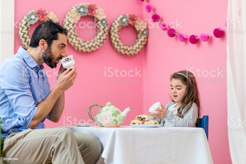 Adult male having a tea party with his young daughter stock photo