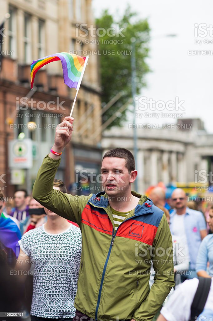 Adult male holds a flag in support of Dublin Pride royalty-free stock photo