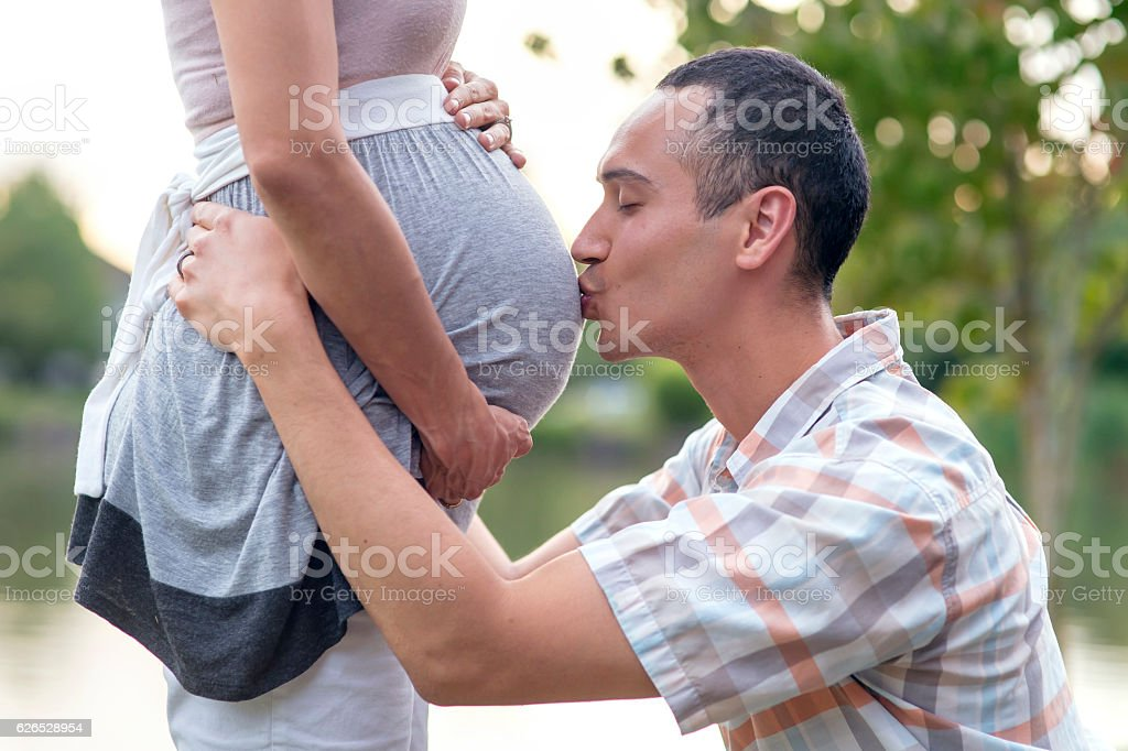 Adult male husband kissing his wife's pregnant belly stock photo