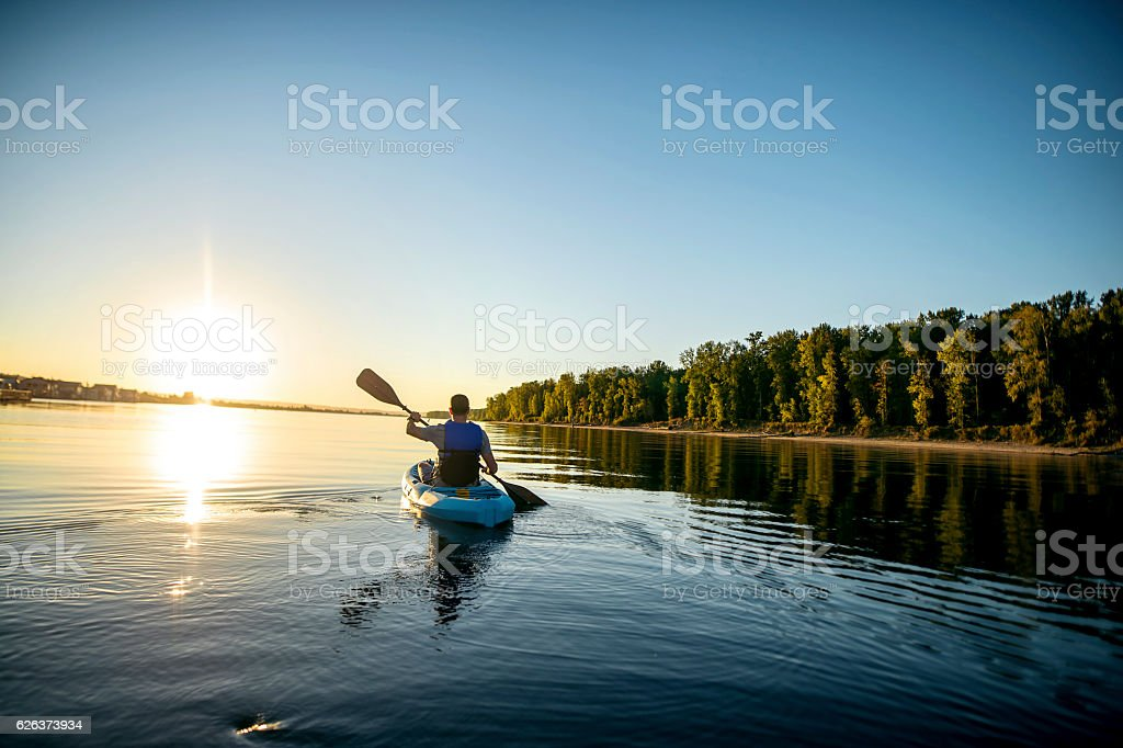 Adult male kayaking in a river at sunset stock photo