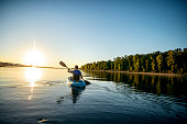 Adult male kayaking in a river at sunset