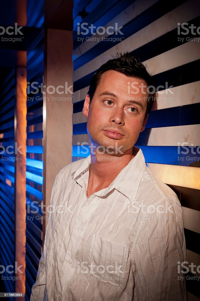 Adult male leaning against a wall in a night club stock photo