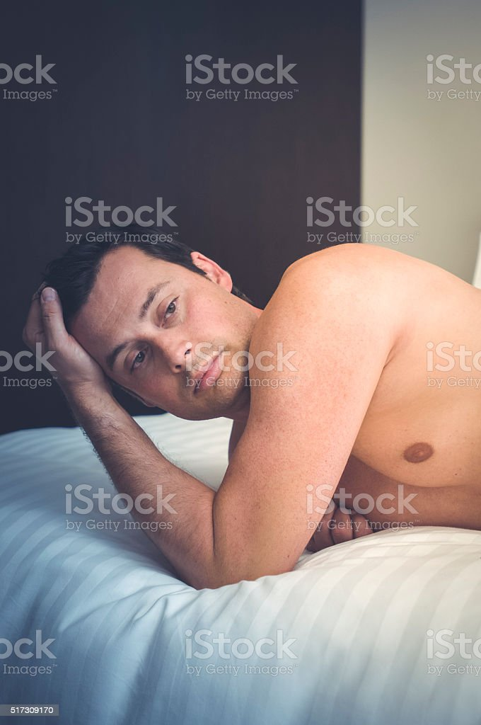 Adult male lying alone on a bed stock photo