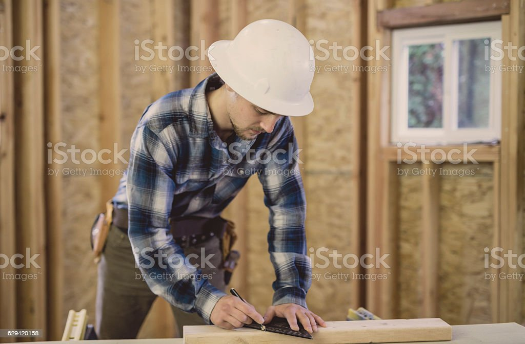 Adult male marking 2x4 for home construction stock photo