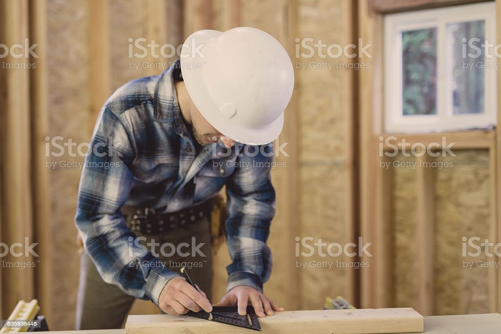 Adult male marking 2x4 for home construction project stock photo