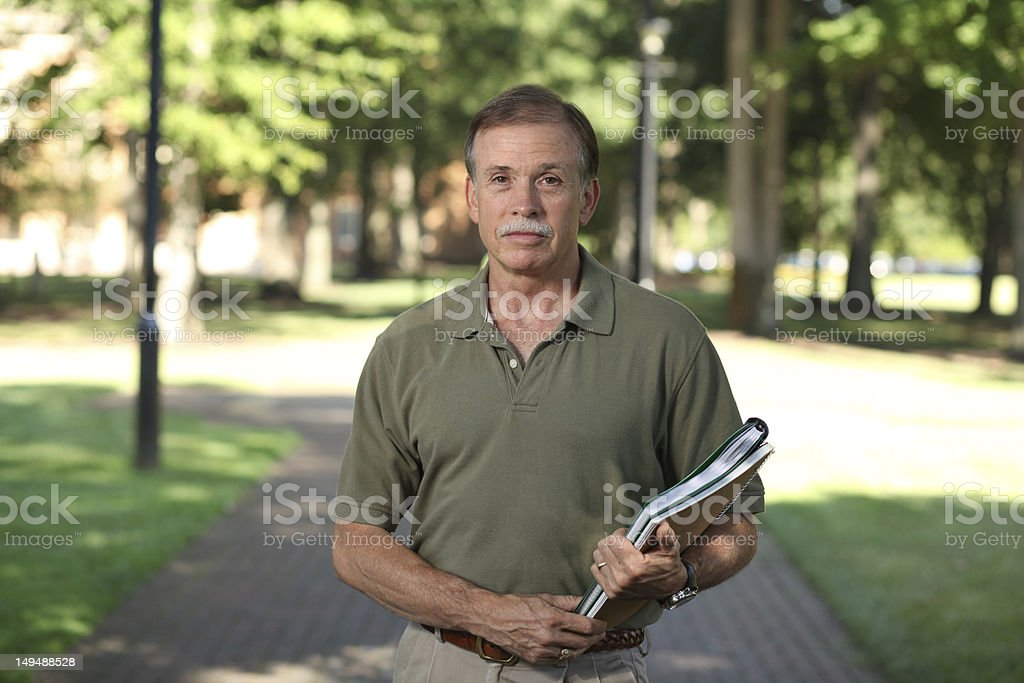 Adult Male outside with school books on campus faces camera. stock photo