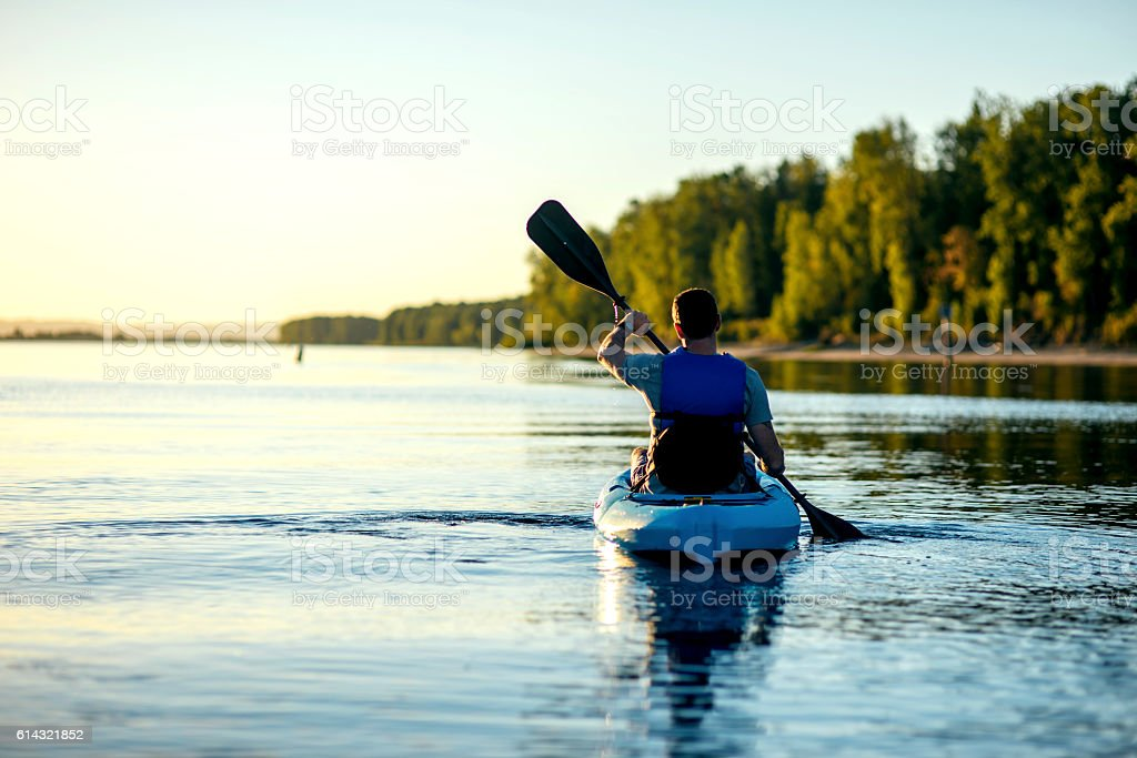 Adult male paddling in a kayak on a river stock photo