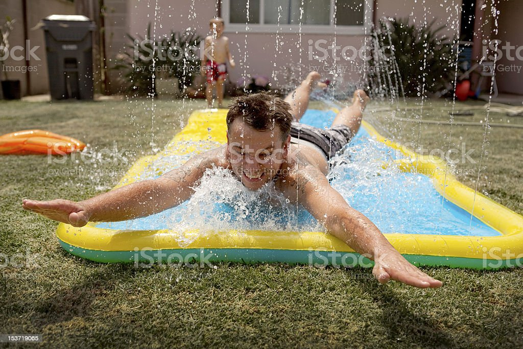 Adult male parent on slip and slide stock photo