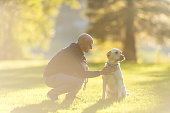 Adult male playing and training his dog in the park