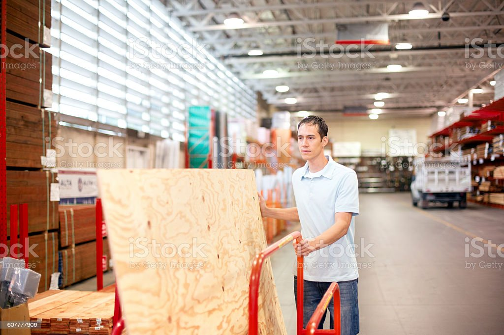 Adult male pushing a cart with plywood sheets stock photo
